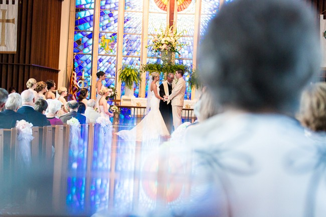 bride and groom taking vows in church in altar with stain glass window reflection