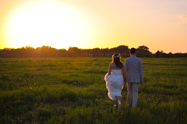 bride and groom walking off into sun set
