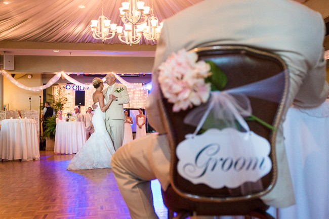 bride dancing with father with groom sitting in chair with a groom sign with a white and pink hydrangea