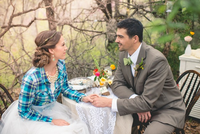 bride wearing blue plaid and groom sitting at a table with lace table runner and pink, yellow and green flowers
