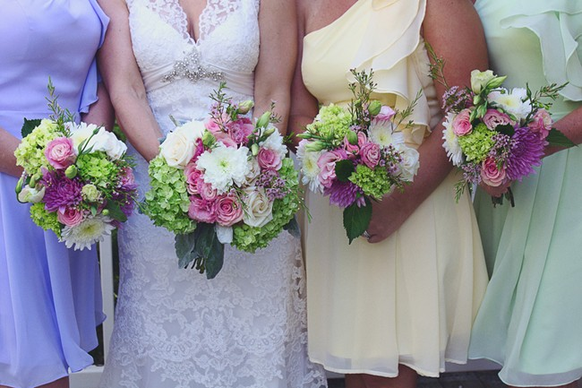 bridesmaids wearing same dress in different colors patel pink yellow and blue with same bouquet