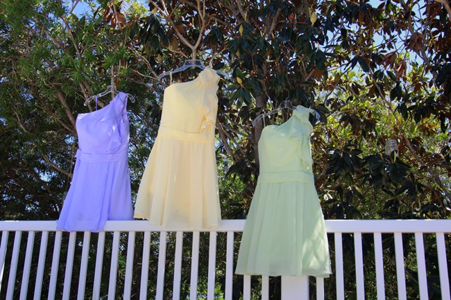 bridesmaids wearing same dress in different colors patel pink yellow and blue