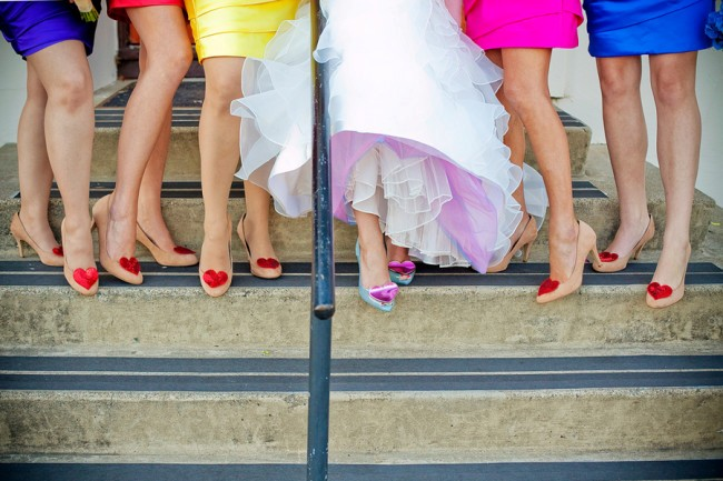 bridesmaids wearing same dress in different colors red yellow blue pink