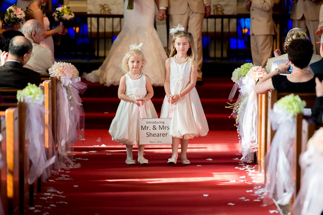 flowers girls at wedding ceremony carrying a sign introducing bride and groom