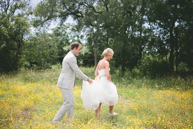 groom helping bride with her dress walking through a feild