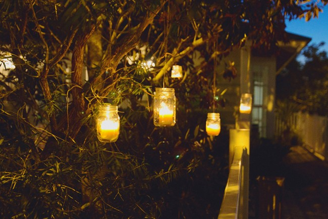mason jars with candles hanging in tree for wedding reception