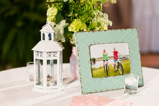 mint green frame with engagement photo and white lantern on wedding reception cocktail table