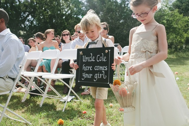 ring bearer and flower girl holding chalk board sign