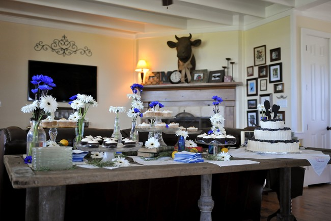 wedding reception dessert table inside with blue and white daiseys
