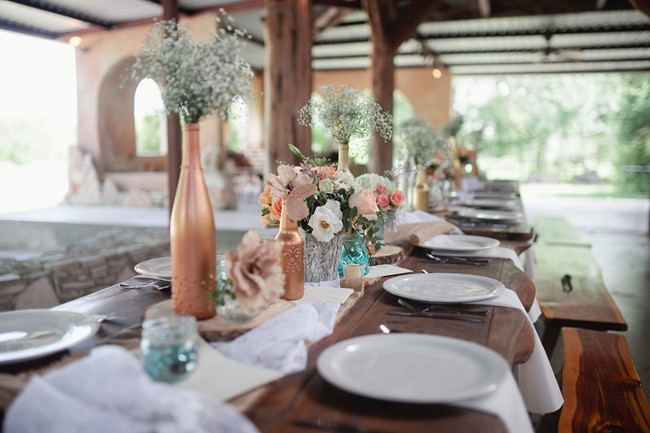wedding reception place setting with bronze vases and babys breath