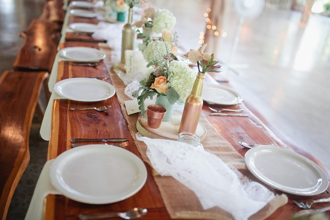 wedding reception table with gold and bronze vase babys breath and burlap runner