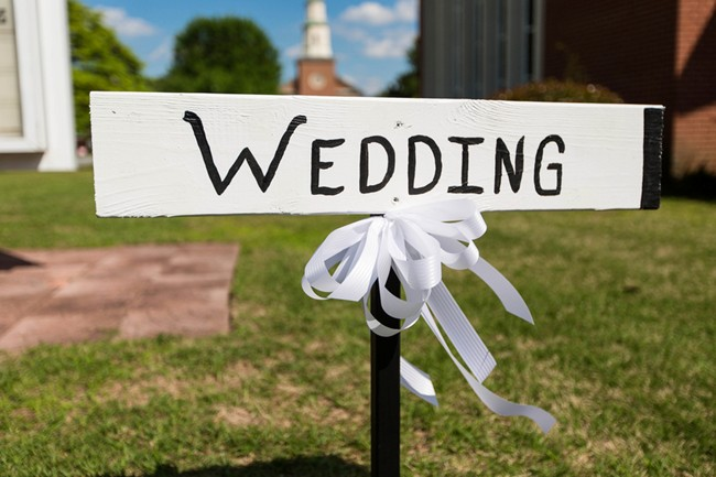 wooden wedding sign with church in the background