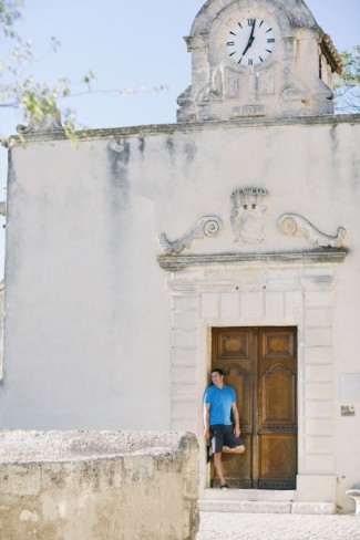 Standing in doorway of stone building in Provence with clock above