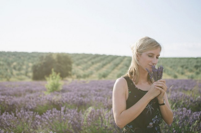 Smelling a bunch of lavender in the fields of provence