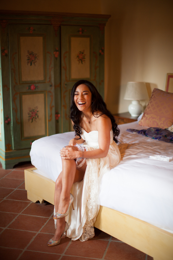 11 bride getting ready sitting on bed puttng garter belt on at Livernano Radda in Chianti Tuscany, Italy wedding