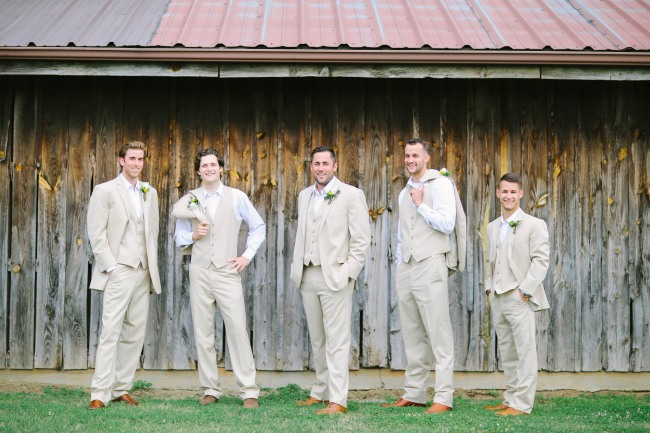 13 Groom and groomsmen standing in front of wooden barn in cream colored suits at  Lindsey Plantation in Greer SC wedding