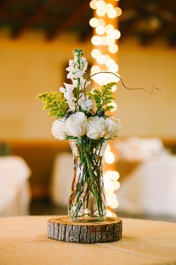 21 white and green wedding reception center pieces on piece of wood at  Lindsey Plantation in Greer SC wedding