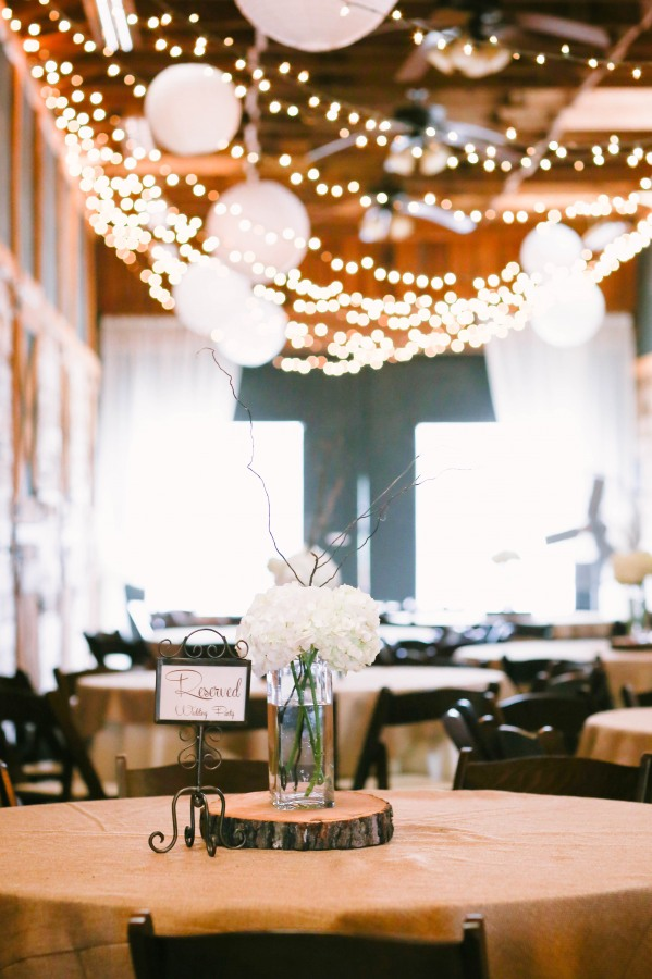 22  Lindsey Plantation in Greer SC wedding reception with white lanterns, white lights and a white and green floral arrangement on table with a reserved signs