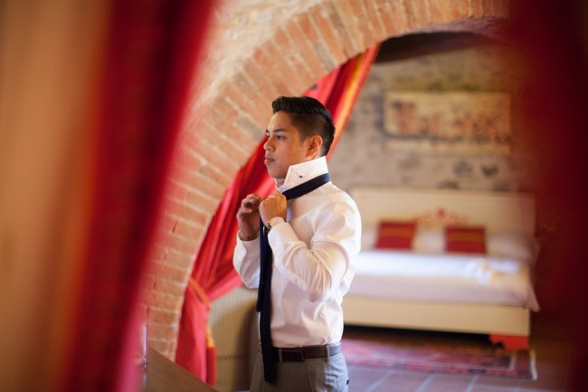 3 Groom tieing tie at Livernano Radda in Chianti Tuscany, Italy getting ready for wedding