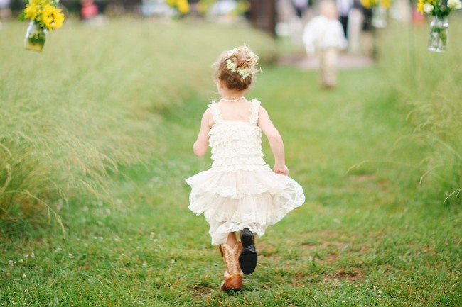 39 Flower girl running up outdoor wedding aisle in field with cow boy boots on at  Lindsey Plantation in Greer SC wedding