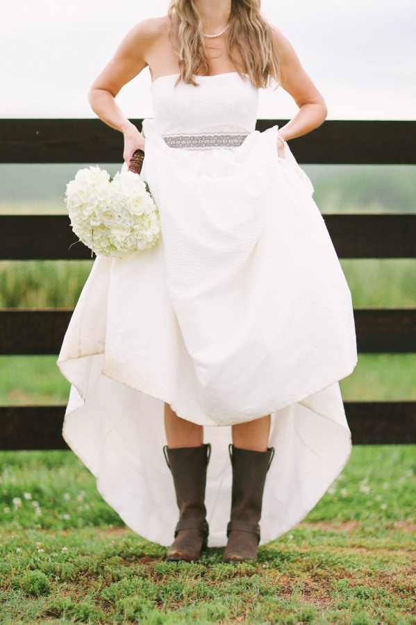 45 Bride wearing cow boy boots infront of frence lifting dress up at ceremony at  Lindsey Plantation in Greer SC