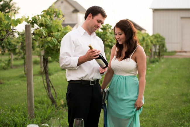 DAVENPORT WINERY engagement shoot couple looking at bottle of wine