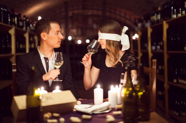 Blindfolded wine tasting couple
