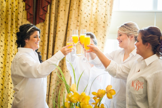 champagne and orange juice toast among bridesmaids and bride