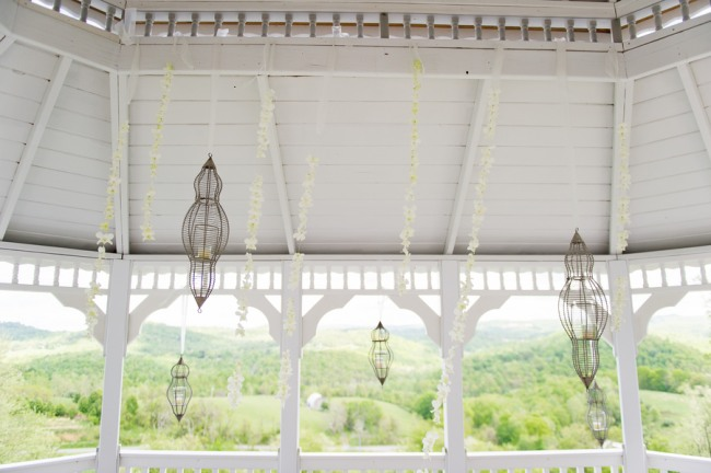 Unique hanging birdcages inside white gazebo