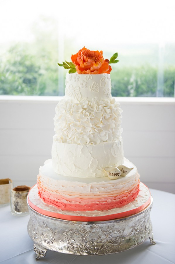 white wedding cake with peach base and orange flower on top