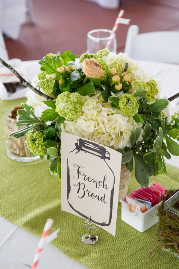 Centerpiece with hydrangeas, willow branches, moss, salmon ranunculas, succulents, peach hypericum berries, viburnum, and celosia