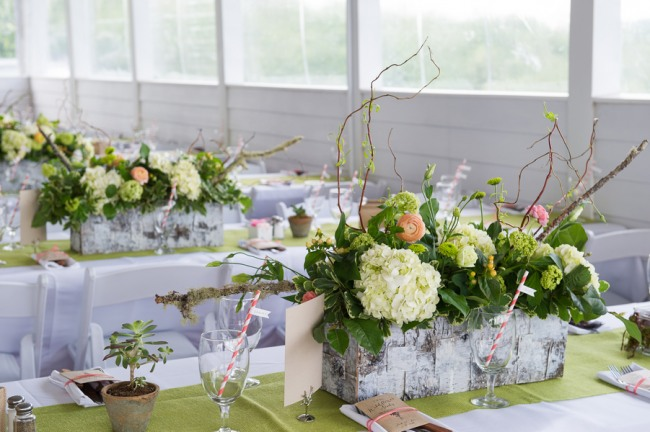 Centerpiece: hydrangeas, sprouted willow branches, moss, salmon ranunculas, succulents, peach hypericum berries, viburnum, and celosia