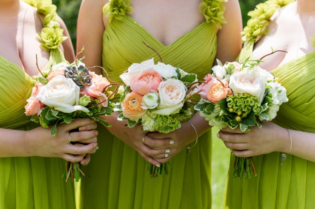Three bridesmaids dressed in lime green floor length gowns with rosette accented straps