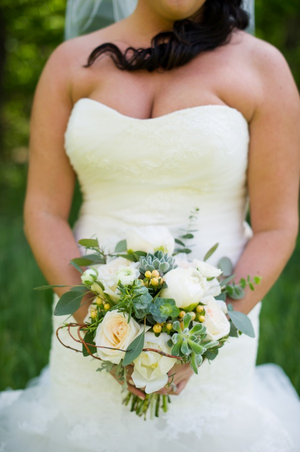bride holding bouquet with white roses
