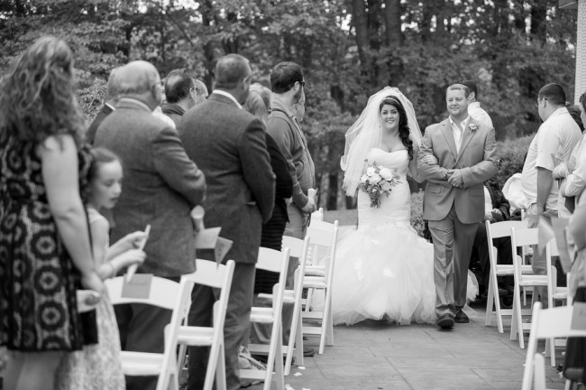 black and white photo of bride walking down the aisle
