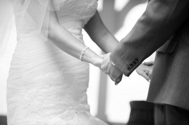 black and white photo of bride and groom holding hands