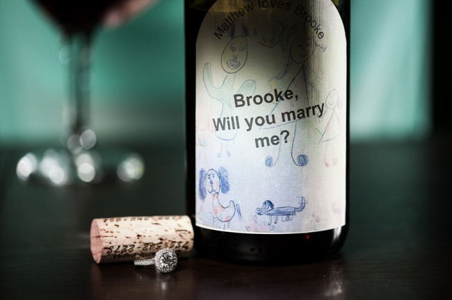 "Personalized wine bottle with the message, ""Brooke will you marry me?"" Cork and ring beside bottle"