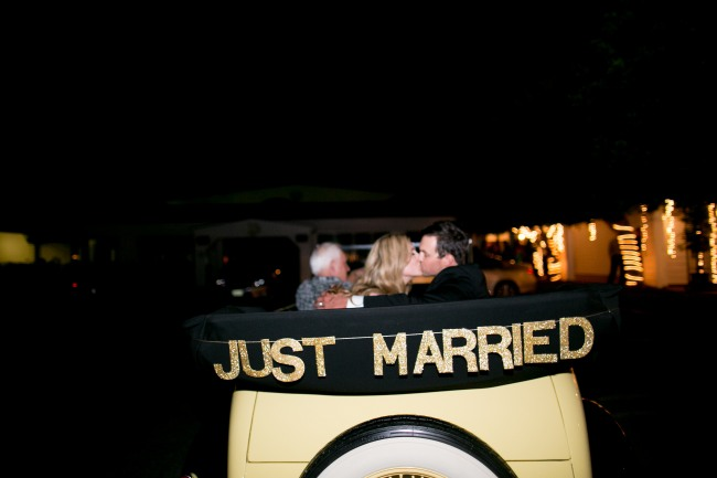 Bride and groom kiss and drive off in 1932 car