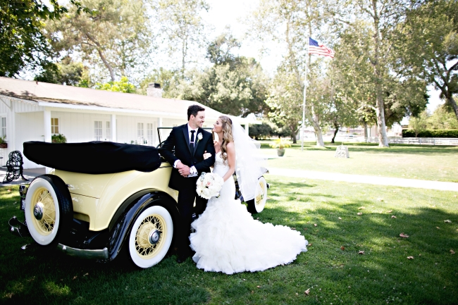 cream colored classic 1932 Chevy convertible with bride and groom
