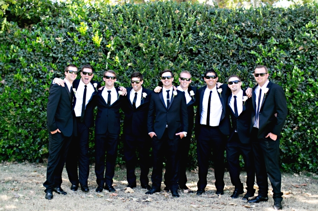 dressed in tuxedos: groom with his groosmen wearing sunglasses