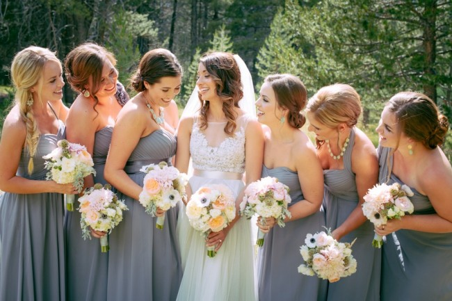 bride wearing illusion neckline wedding gown with bridesmaids wearing grey dresses