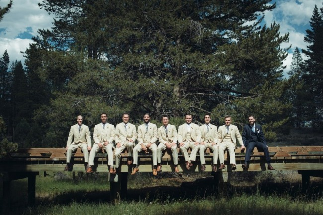 groom with groomsmen wearing beige suits while groom is in black