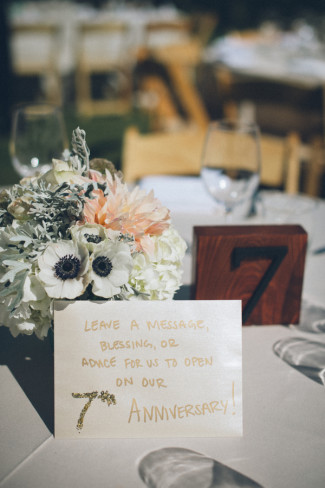 Outdoor wedding in sierra dessert with a wooden table number and an envelope with peach and white center piece