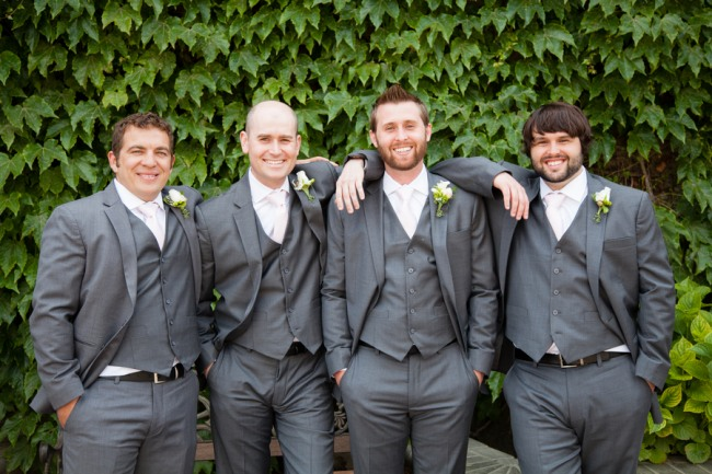 Groom and groomsmen in charcoal gray standing in front of leaf wall at Guglielmo Winery wedding