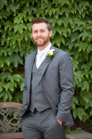 Groom in charcoal gray standing in front of leaf wall at Guglielmo Winery
