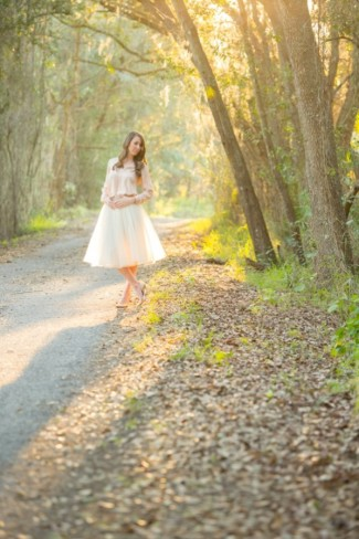 16 Maternity photo twins announcement women standing in path in forest holding bellly