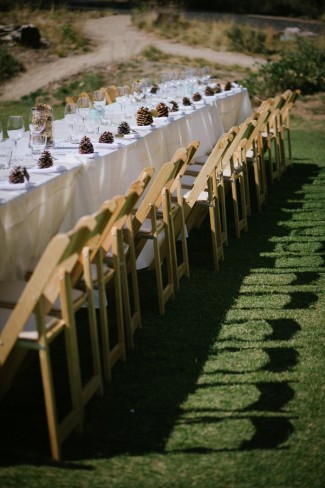 Outdoor wedding reception in Sierra Nevada mountains white table with pine cone at each place setting