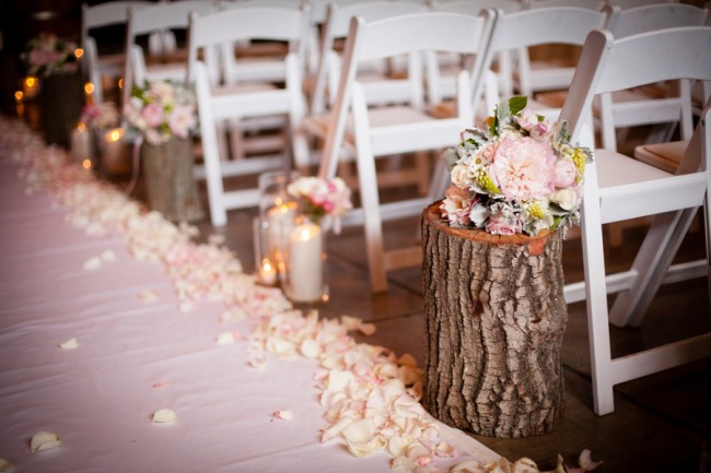 Wood stumps line wedding ceremony aisle with white runner and rose petals