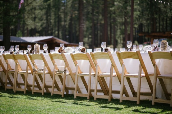 wedding reception at PJ's Bar and Grill - groom and brides chairs with a sparkly arrow and pine cones