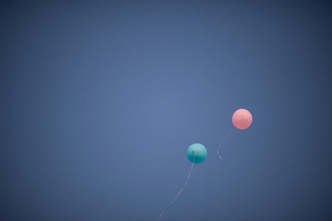 Pink and blue geronimo balloons floating away in the blue sky